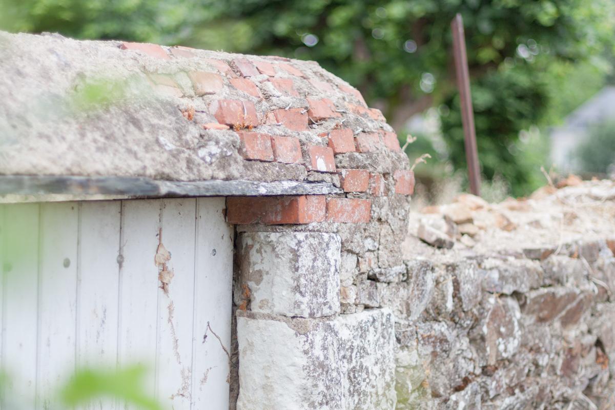 Vieille porte, muret en pierres et en briques